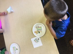 Birds eye view of child sitting at a desk with an apple on a plate on the desk