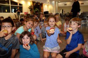 5 children sitting together holding apples