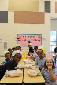 children sitting at lunch table in cafeteria